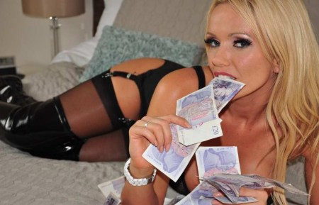 Naughty blonde Lucy Zara teases with her pay piggy cash on the bed in sexy black lingerie and leather boots