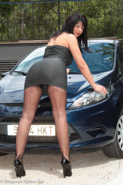 MILF Desyra Noir in black nylons with garters posing by a car