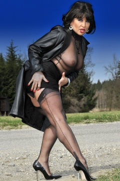 German MILF outdoor tease in black nylons, spiked heels, coat, upskirt pics